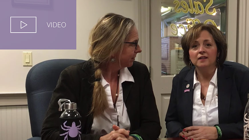 Video still of Jennifer Platt and Beth Carrison and white sans-serif type in upper left on muted lavender background with video icon