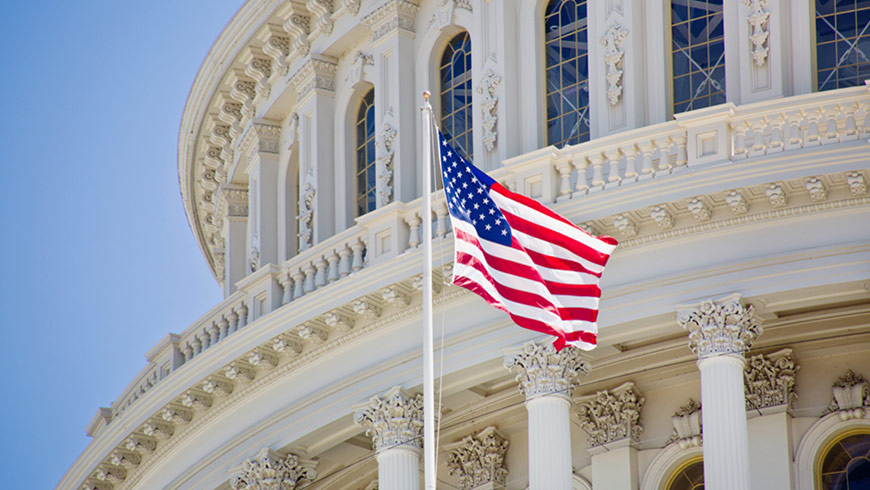 A United States national flag in front of the Capitol building in Washington DC